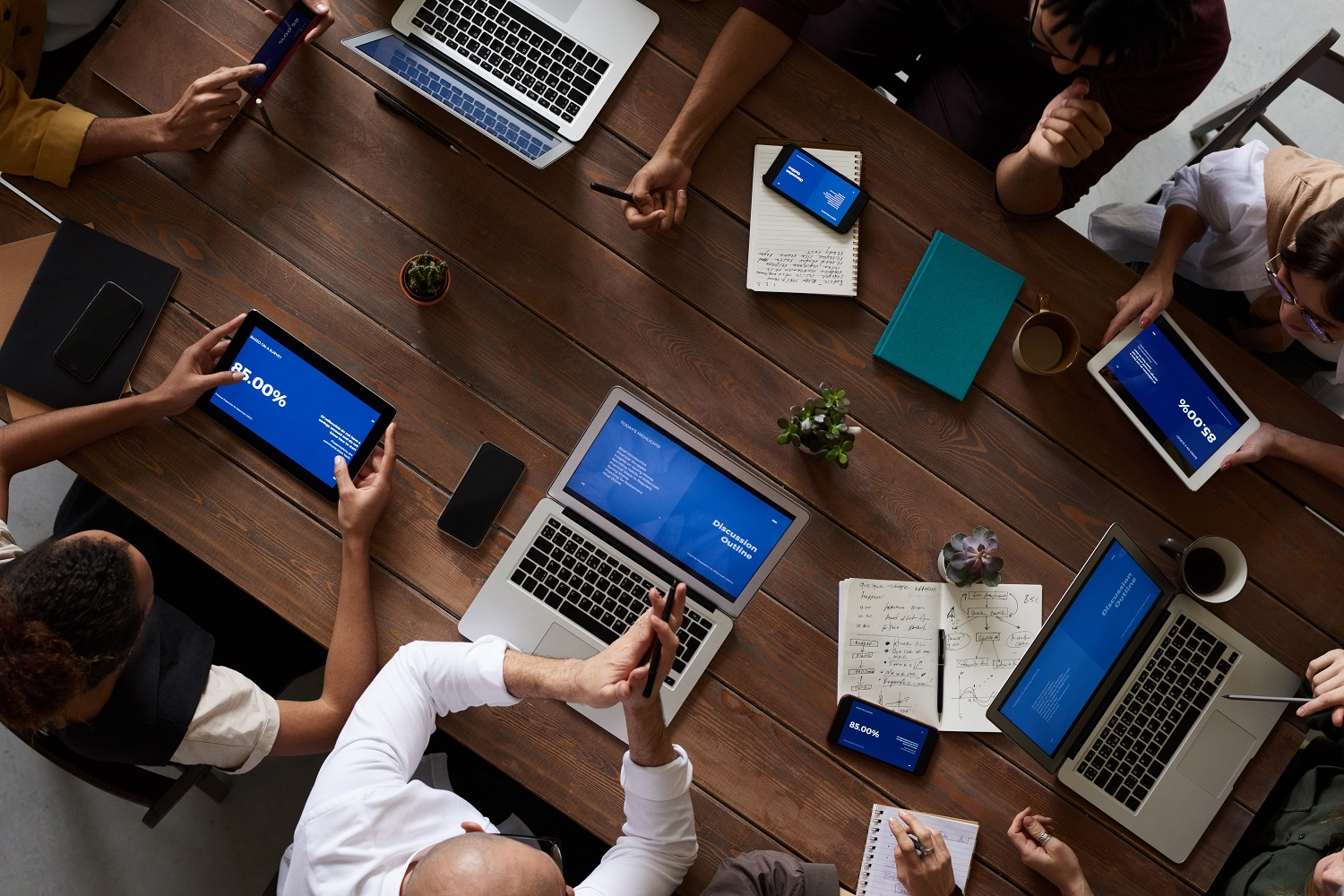 Business people working with laptop computers and tablets at a conference table