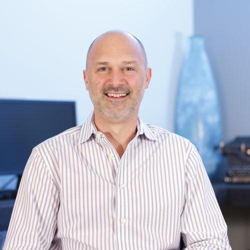 A portrait of Nick Calvert, founder of Computer Geeks, wearing a dress shirt