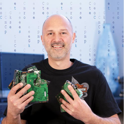 """A portrait of Nick Calvert, founder of Computer Geeks, wearing a t-shirt, holding computer parts, in front of a """"Matrix"""" style background"""